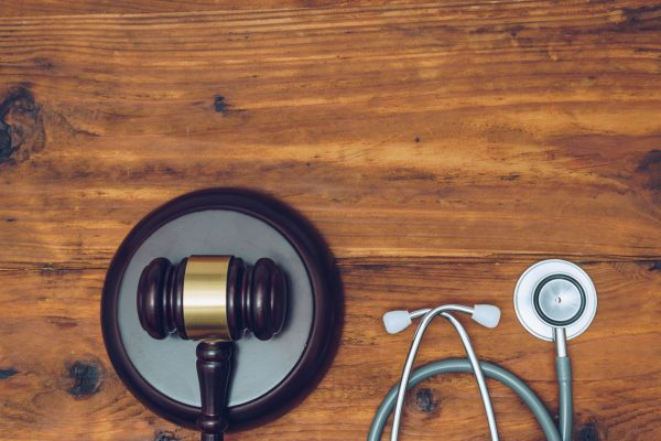 Stethoscope with judge gavel. Concept of healthcare and medicine, malpractice, legal system.